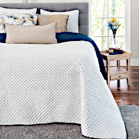 Creme satin quilt set with navy stitching and matching shams.