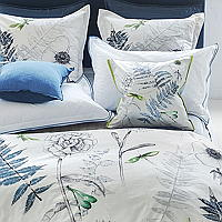 An elegant floral bedding design by Designers Guild featuring graphically drawn linear flowers and ferns.