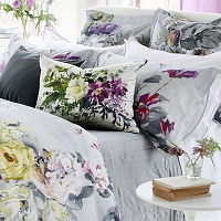 This statement floral bedding design is an ornate composition of flowers and foliage set against a dramatic painterly sky texture in cool gray.
