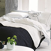 Luxuriously soft and lightweight 100% silk quilts and shams in striking white with a reverse of noir black. Hand-quilted and finished with a contrast cross stitch detail makes for a sophisticated complement to any bedroom.