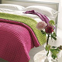 Luxuriously soft and lightweight 100% silk quilts and shams in a vibrant lime green with a reverse of fuchsia pink. Hand-quilted and finished with a contrast cross stitch detail makes for a sophisticated complement to any bedroom.