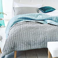 Luxuriously soft and lightweight 100% silk quilts and shams in a delicate pebble grey with a reverse of duck egg.