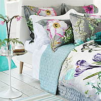Expressive and highly detailed floral bedding with hand-painted flowers arranged on a softly shaded ground.
