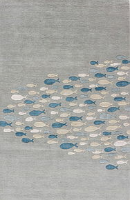 This playful hand-tufted area rug showcases a contemporary design and cool-toned coastal hues.