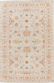 Timeless with an antique floral design, this hand-tufted wool rug boasts a classic pattern of scrolling vines and medallion-style blooms.