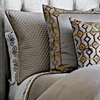 The ensemble features decorative pillows in a pewter color poly silk with antique gold embroidery and includes Laura Solid and Quilted Stone bedding pieces.