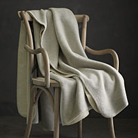 A reversible blanket with a crafted whip-stitched edge.