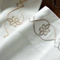 Concerto sateen sheeting is adorned with an airy wave of embroidery.