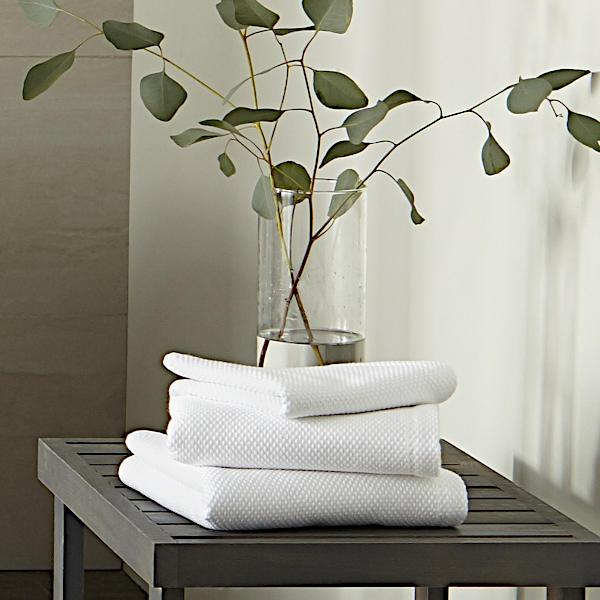 Peacock Alley Spa Bath Towel and Bathrobe - Towel on table.