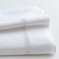 Organza sheeting features an inset of white trim on Traditions Linens's Italian sheeting.